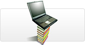 A laptop perched on a tall stack of books
